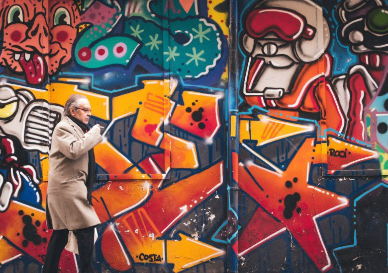 Older person walking by a wall with graffitis; photo by javier-garcia on Unsplash