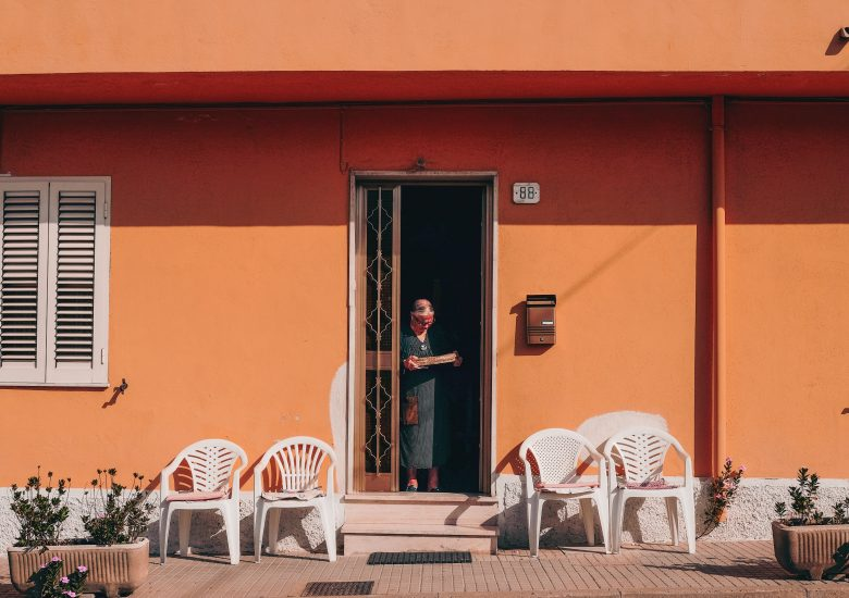 Photo of an older woman on her sunny doorstep by cristina-gottardi on unsplash
