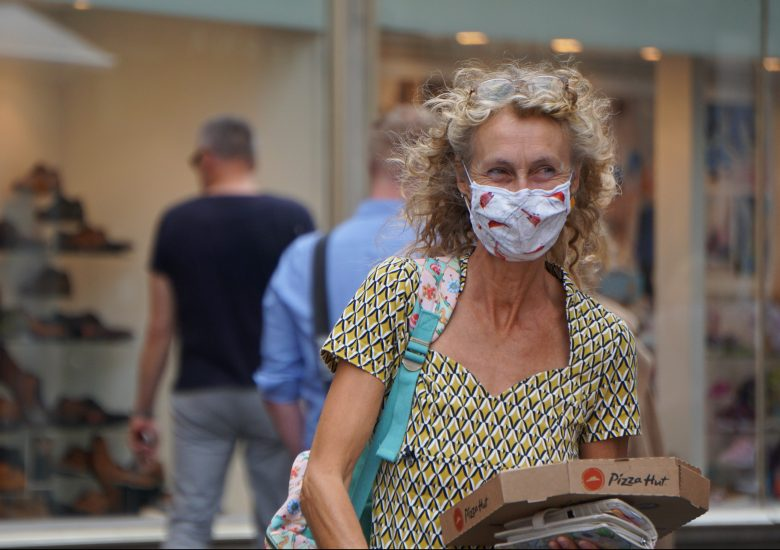 Photo of a middle-aged woman in the street wearing a mask by georg-arthur-pflueger on Unsplash